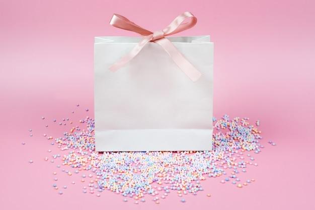 Geschenk in weißer papiertüte mit regenbogenfarbenen bonbons