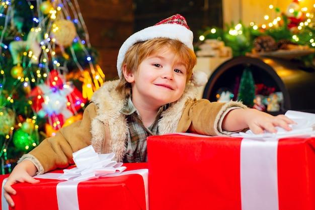 Geschenk kinder emotionen. neujahrs-weihnachtskonzept. glückliches kind, das spaß mit großer geschenkbox hat. kind, das spaß nahe weihnachtsbaum drinnen hat. weihnachtskinder - glückskonzept.