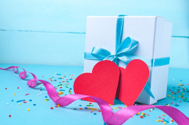 Geschenk, kleine schachtel mit einem blauen satinband und roten herzen gebunden. geschenk-konzept. überraschungen und geschenke für die liebsten. herzlichen glückwunsch zum urlaub