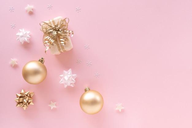 Geschenk, kugeln, grußkarte, goldene verzierungen auf pastellrosa oberfläche