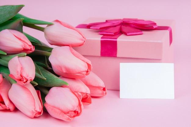 Geschenk mit blumen tulpen auf einem rosa hintergrund für valentinstag, für muttertag, verspotten