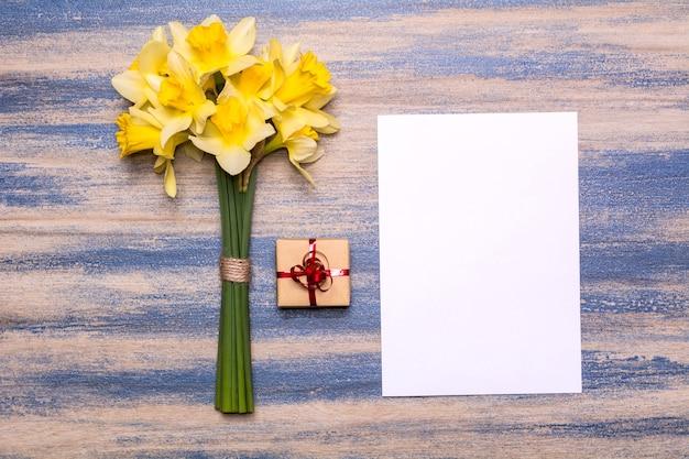 Geschenk mit einem roten band, einem stück papier und einem strauß narzissen