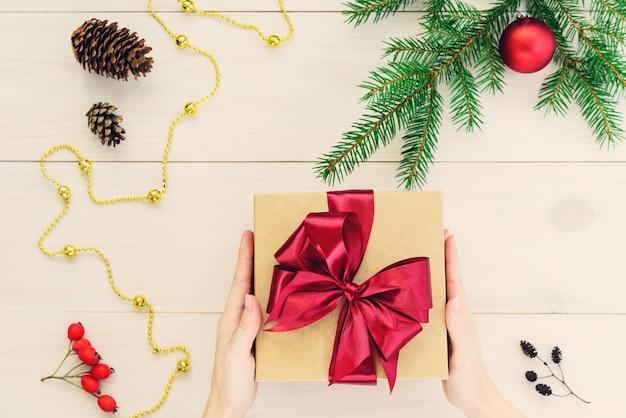 Geschenk mit einem roten band in den händen für weihnachten und neujahr auf einem hölzernen hintergrund