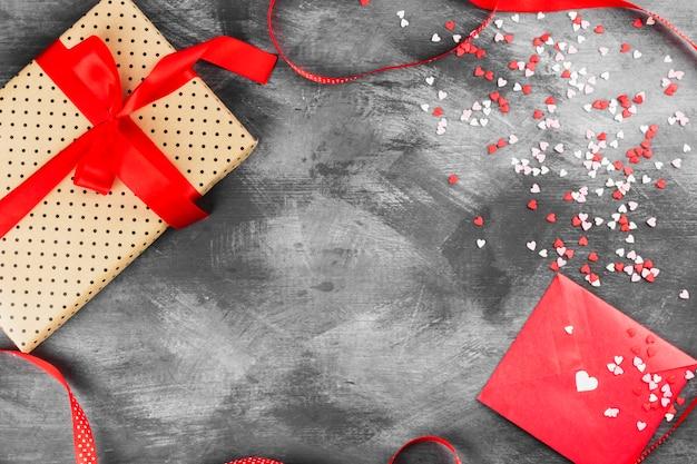 Geschenk mit einer bürokratie, einem liebesbrief hängt am seil und herzen auf einem dunklen hintergrund. draufsicht, kopie, raum