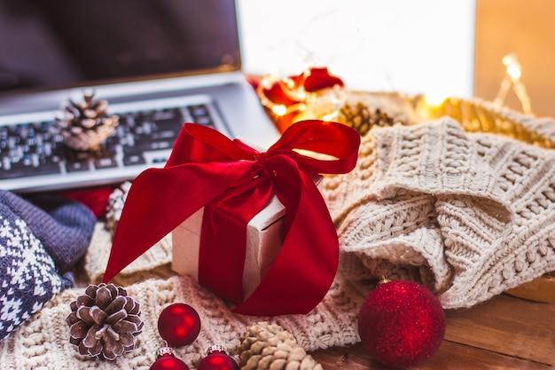 Geschenk mit einer roten schleife und laptop-weihnachtskegeln und einem leichten gestrickten schal weihnachten online-shopping
