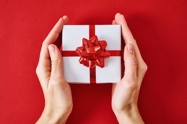 Geschenk mit festlichem band in den händen einer frau
