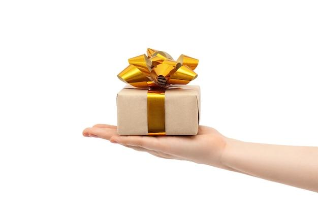 Geschenk mit goldenen schleifen in der hand einer frau.