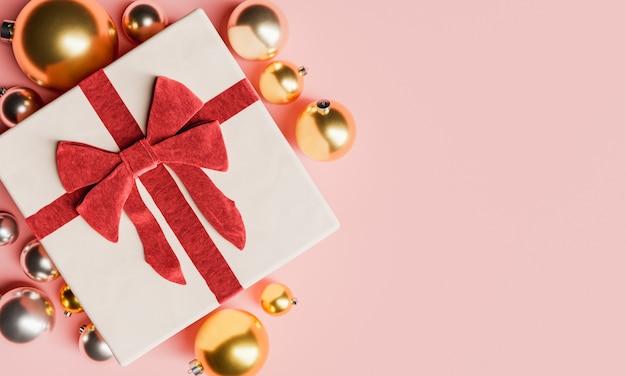 Geschenk mit großer schleife und weihnachtskugeln herum