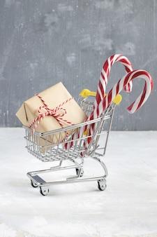 Geschenk mit kraftpapier, zuckerstange und rot-weiß gedrehter kordel im kleinen einkaufswagen.