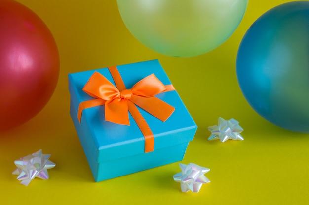 Geschenk mit orange schleife und bunten luftballons auf gelb