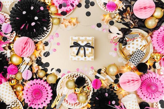 Geschenk mit partydekorationshintergrund. gold, schwarz und rosa farbe. flache lage, ansicht von oben