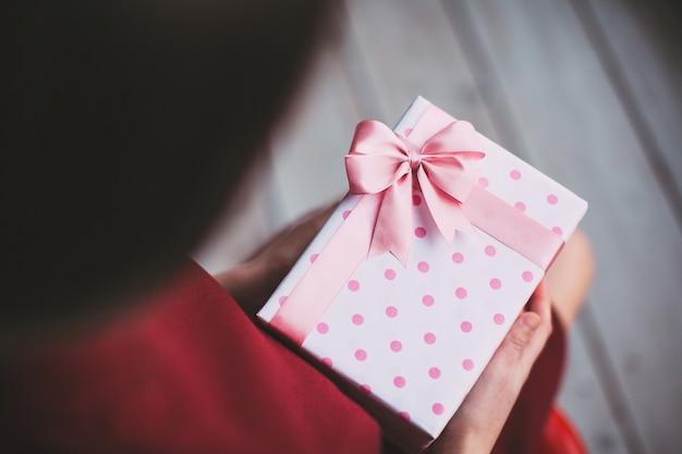 Geschenk mit rosa band in den weiblichen händen