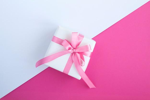 Geschenk mit rosa schleife in der mitte der zweifarbe.