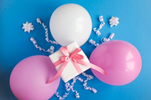 Geschenk mit rosa und weißen luftballons auf dem blauen tisch. draufsicht. nahansicht.