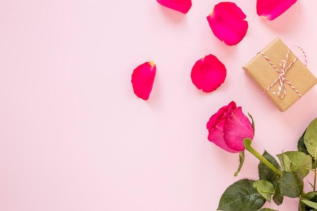 Geschenk mit rose und blütenblätter zum valentinstag