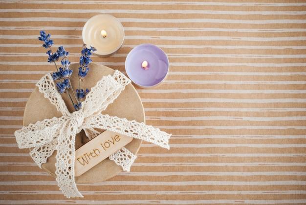 Geschenk mit spitzenschleife, lavendelblüte und brennender kerze