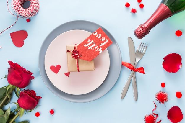 Geschenk mit tag auf platte in der nähe von besteck, rosen und einer flasche champagner