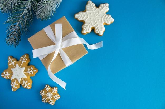 Geschenk mit weißem band und weihnachtskuchen