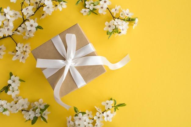 Geschenk mit weißem bogen und blühenden ästen auf dem gelben hintergrund
