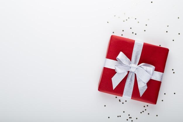 Geschenk oder geschenk box und sterne konfetti auf farbtabelle draufsicht. flache laienkomposition für geburtstag, muttertag oder hochzeit.
