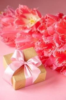 Geschenk- oder geschenkbox mit schönem strauß rosa tulpenblumen auf rosa oberfläche