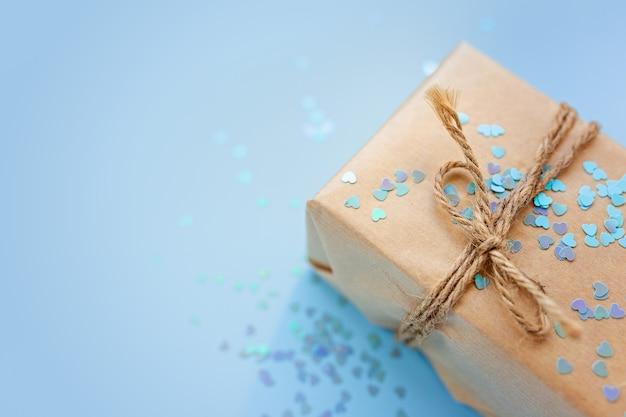 Geschenk- oder geschenkbox verpackt in kraftpapier mit seil und glitzer funkelt herzen auf blauem hintergrund draufsicht. flat-lay-styling. kopieren sie platz für text. feiertagskartenkonzept. nahaufnahme