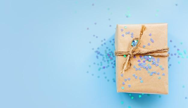 Geschenk- oder geschenkbox verpackt in kraftpapier mit seil und glitzer funkelt herzen auf blauem hintergrund draufsicht. flat-lay-styling. kopieren sie platz für text. feiertagskartenkonzept. neujahr, valentinstag
