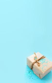 Geschenk- oder geschenkbox verpackt in kraftpapier mit seil und glitzer funkelt herzen auf blauem hintergrund draufsicht. flat-lay-styling. kopieren sie platz für text. feiertagskartenkonzept. vertikal