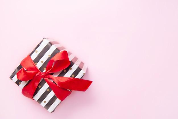 Geschenk oder präsentkarton in den weißen und schwarzen streifen mit einem roten bandbogen lokalisiert auf rosa tischplatteansicht.