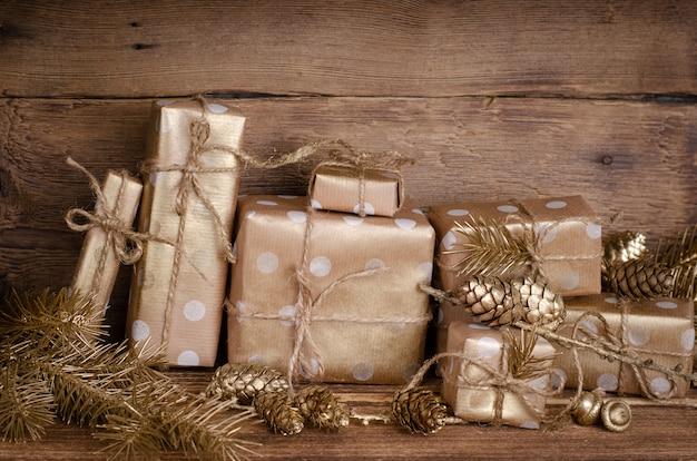Geschenk- oder präsentkartons in kraftpapier mit goldenen verzierungen eingewickelt