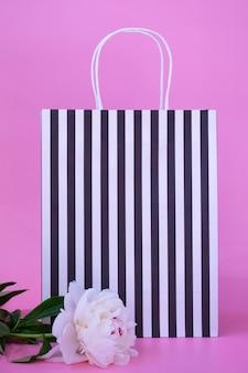 Geschenk-ökotasche in schwarz-weiß-streifen mit kopienraum auf farbigem hintergrund mit einer weißen schönen pfingstrose. geschenk-konzept. vertikales foto