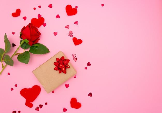 Geschenk, rose und rote herzen auf rosa hintergrund