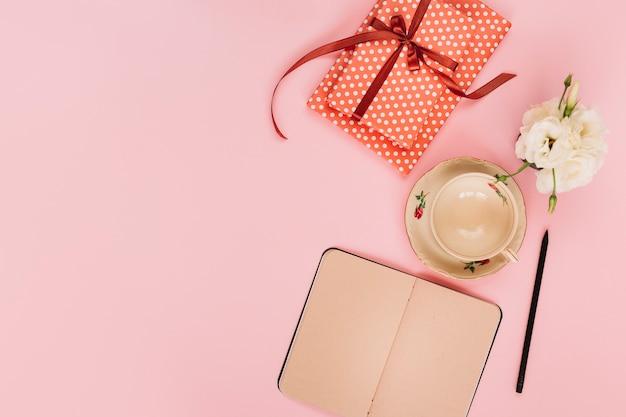 Geschenk und blume in der nähe von tasse und notebook