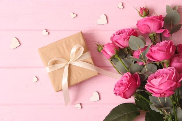 Geschenk und blumen auf einem farbigen hintergrund urlaub geben ein geschenk glückwünsche
