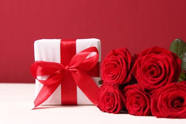 Geschenk und blumen auf einem farbigen hintergrund urlaub geben ein geschenk