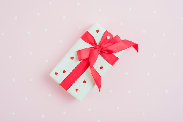 Geschenk und herzen auf rosa hintergrund