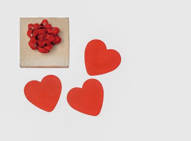 Geschenk und herzen isolieren. geschenkkarton mit roter schleife und drei roten herzen auf weißem hintergrund