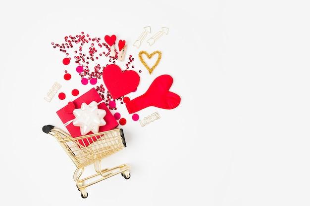 Geschenk und konfetti in einem warenkorb auf weißem hintergrund. valentinstag einkaufen. flache lage, ansicht von oben