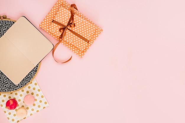 Geschenk und notizbuch in der nähe von makronen