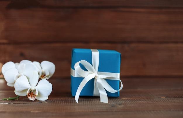 Geschenk und orchidee. das konzept der feier und eine willkommenskarte.