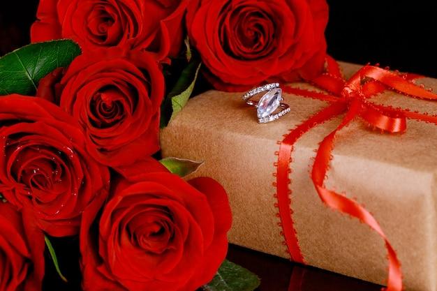 Geschenk und ring mit schönen roten rosen auf schwarzem hintergrund. valentinstag konzept.