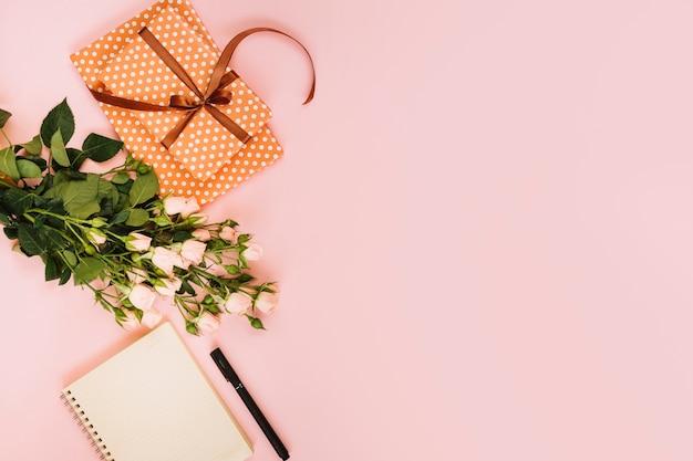 Geschenk und rosen nahe notizblock