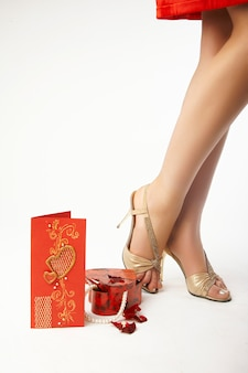 Geschenk- und valentinskarte neben weiblichen beinen
