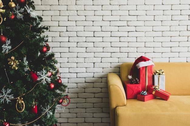 Geschenk verpackt auf gelbem sofa und verziertem weihnachtsbaum mit weißer backsteinmauer.