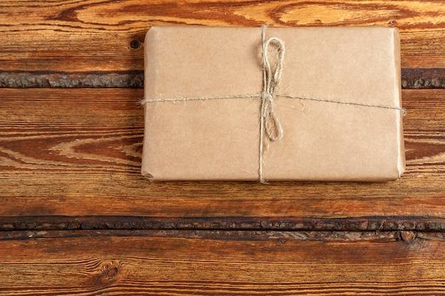 Geschenk verpackt in der umweltfreundlichen biologisch abbaubaren pappe auf dunklem altem hölzernem hintergrund mit leerstelle für text