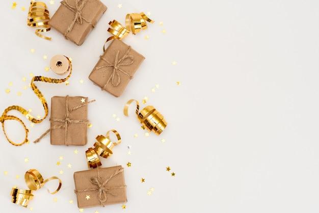 Geschenk, weihnachtsgoldene dekorationen, zypressenzweige, kiefernkegel auf weiß