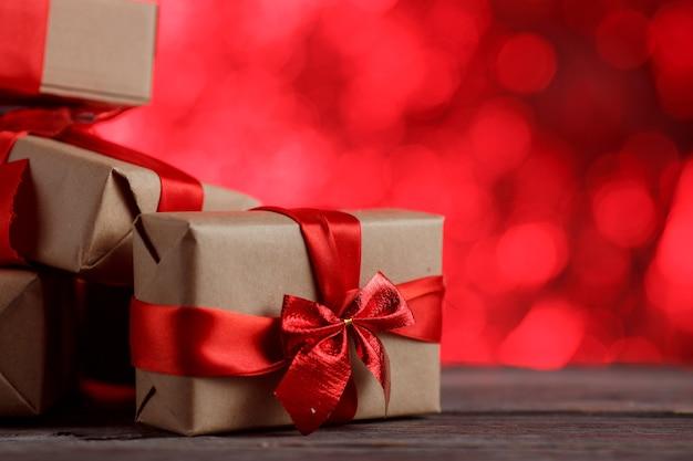 Geschenk weihnachtskiste mit band auf holztisch gegen abstrakten roten hintergrund.