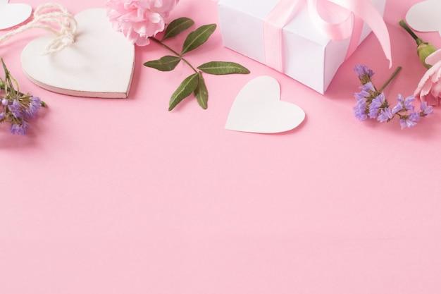 Geschenk, weißes hölzernes herz und blumen auf rosa hintergrund