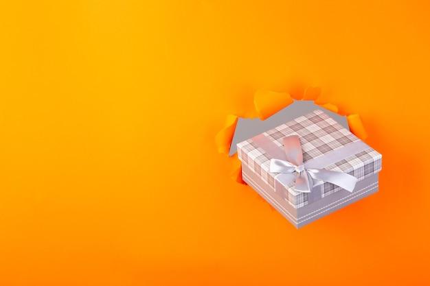 Geschenk zeigt durch ein orange zerrissenes papier
