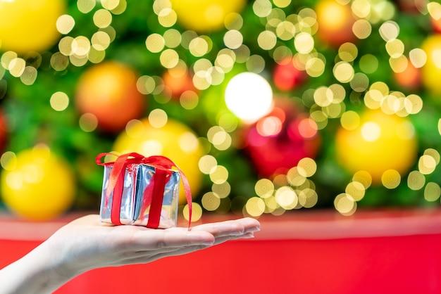 Geschenk zur hand mit weihnachts-bokeh-lichtern